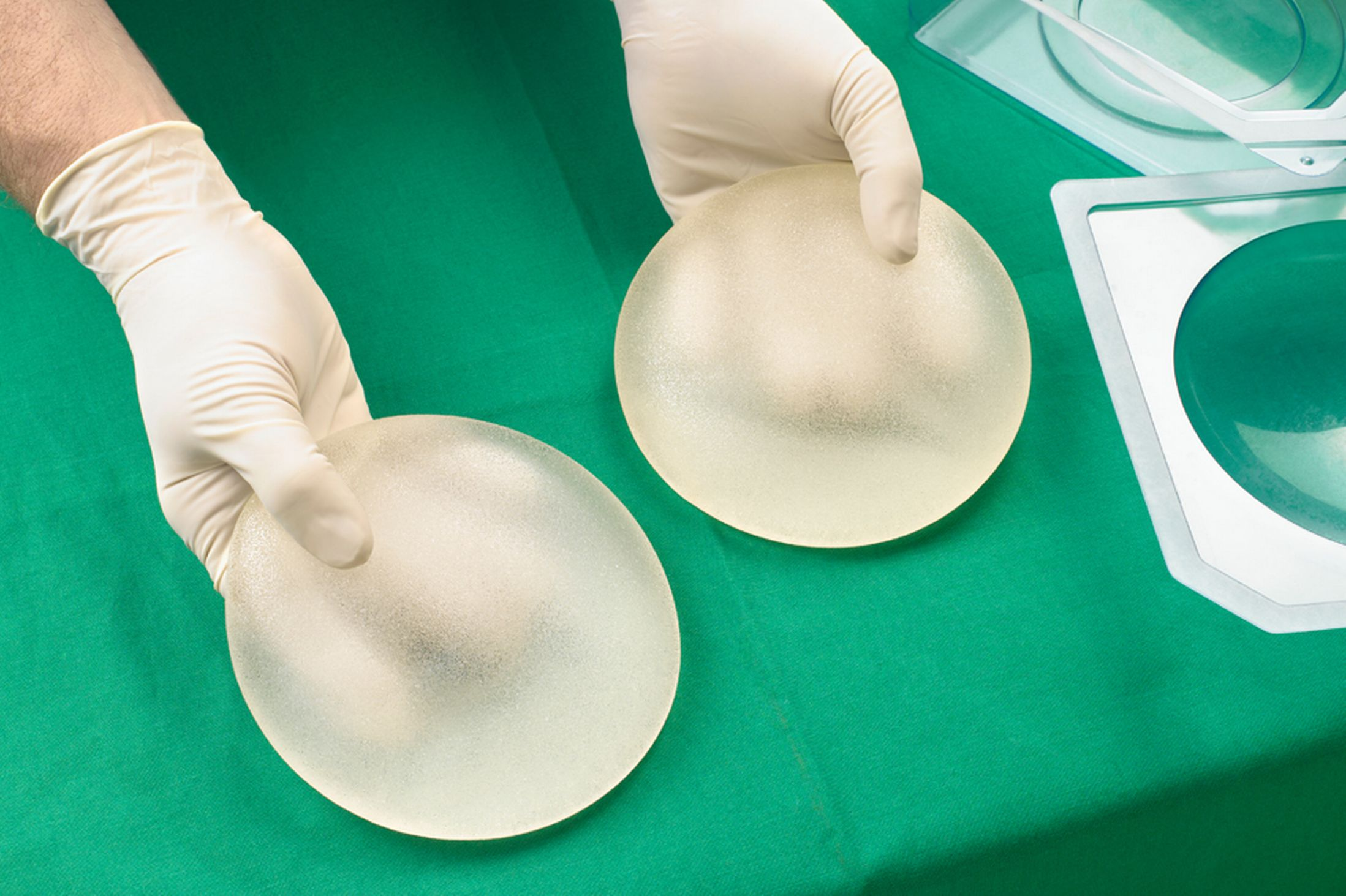 Surgeon-holding-silicone-breast-implants